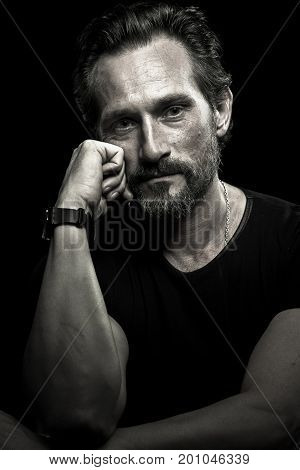 Confident brutal male isolated on black background. Monochrome portrait of satisfied man.