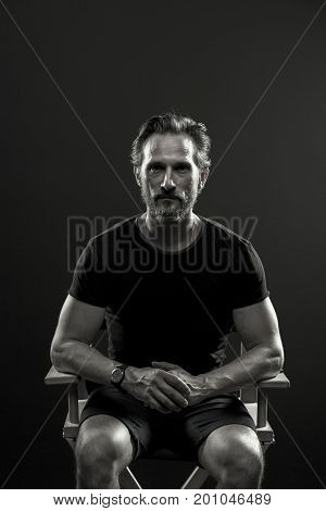 Studio portrait of mid aged man sitting on chair. Male in t-sirt and shorts holding hands on knees.