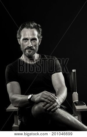 Black and white portrait of strong mature man. Beardy male showing satisfied emotion.