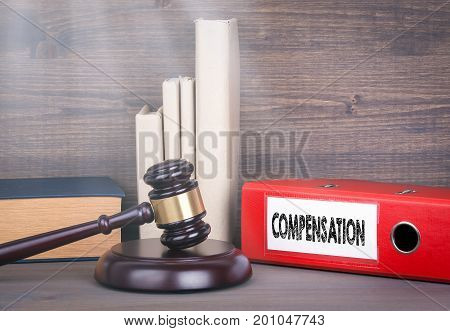 Compensation. Wooden gavel and books in background. Law and justice concept.