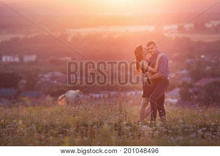 man and girl in love romantic lovers kissing hugging at sunset sunrise on the background of mountains and fog sun clouds in fiery red orange colors. Concept wedding first kiss love date. copyspace