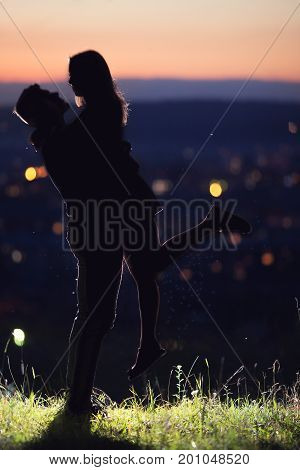 Lovers man and girl against background night city night starry sky and horizon. Concept date Valentine's Day first kiss love forever together.