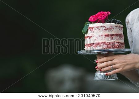 Anonymous woman in white dress holding platter with beautiful cake.