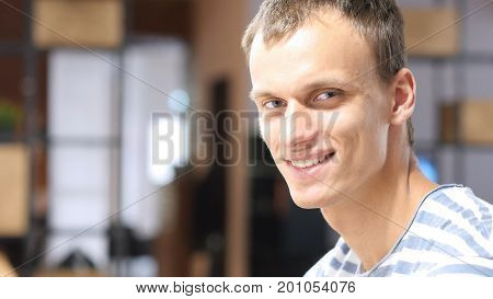 Happy Mid-adult Businessman Sitting At Office, Laughing Portrait