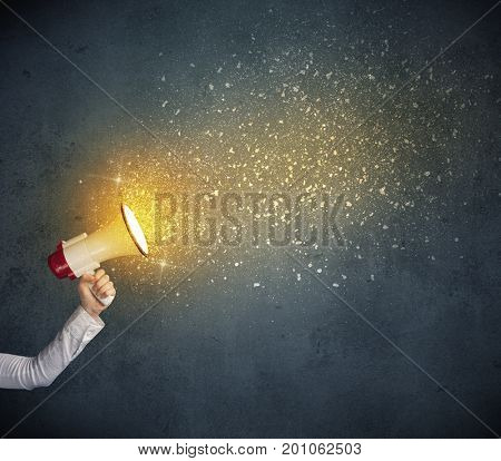 Caucasian business hand holding megaphone with yellow sparkles