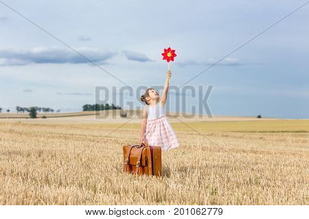Girl In Classic Dress With Travel Suitcase And Pinwheel Toy