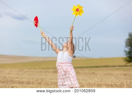 Little Girl In Classic Dress Holding Pinwheel Toys