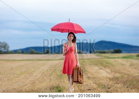 Portrait Of Young Woman With Suitcase And Umbrella