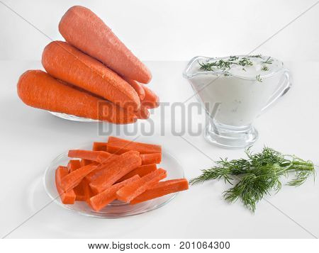Carrot sticks whole fresh carrots and sour cream sauce with herbs healthy dietary healthy food on a white background in glass plates and in a glass sauce boat