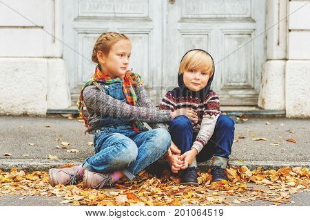 Autumn portrait of 2 adorable kids in a city wearing warm pullovers and denim jeans