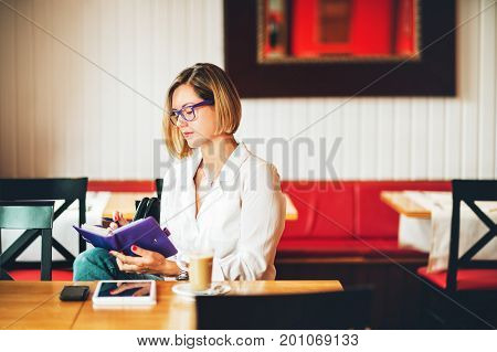 Young successful business woman writing in agenda girl working in coffee shop