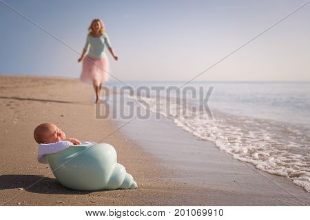 Beautiful woman running to her newborn baby boy on the sandy ocean beach. Happy mother meeting her child. Newborn baby in the nutshell on the sea shore on sunny day. Motherhood and childhood concept.