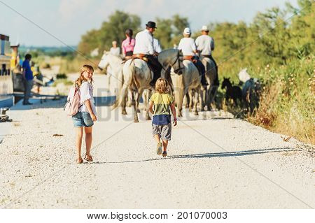 Kids tourists enjoying a trip to South of France white wild horse in Parc Regional de Camargue - Provence.