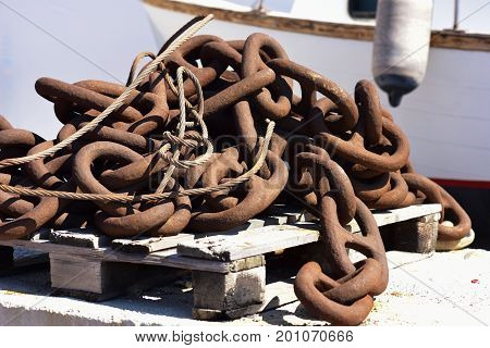 Large rusty chain for the naval industry over a wooden pallet