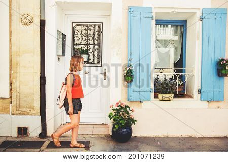 Funny little girl traveler walking on the streets of Provence wearing backpack. Travel with kids family vacation on south of France image taken in Aigues-Mortes Camargue