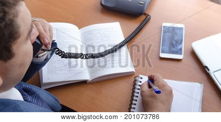 A businessman speaks on a landline phone and makes notes in a notebook. Nearby lies the phone and open book.