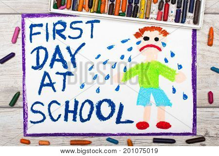 Photo of colorful drawing: Words FIRST DAY AT SCHOOL and sad crying little boy