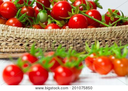 Fresh cherry tomato on wood basket. Close up lovely cherry tomato for background or wallpaper. Prepare fresh cherry tomato for home cooking look so delicious. Side view selective focus on background. Red cherry tomato concept.