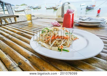 Pad Thai on white dish at outdoor restaurant on the beach