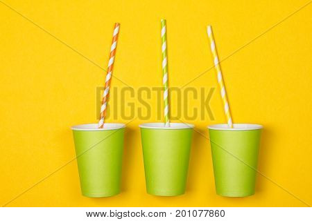 bundle of multi-colored drinking straws in a paper Cup on a yellow background. fashion minimal. flat lay