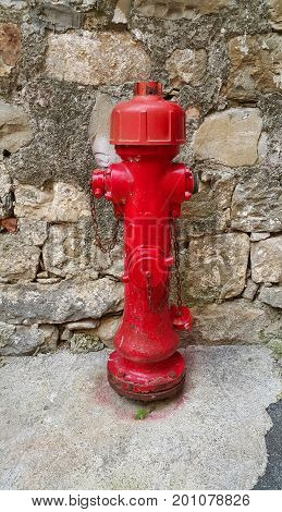 Red old fireplug against a stone wall background