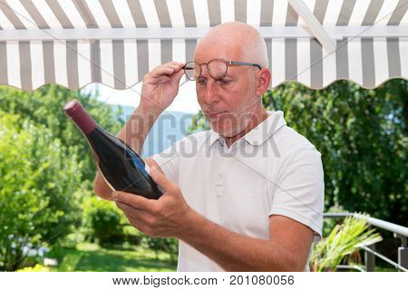 mature man with a bottle of red wine on the terrace