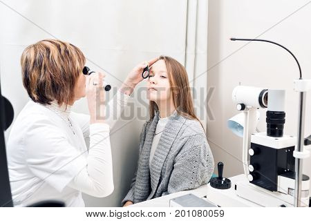 Senior female optometrist examining young woman's eyes in private clinic.