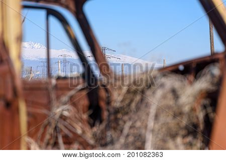Power line and snow cap mountains seen trough rusty car window with hay growing inside old Russian Soviet made car in Southern Armenia on sunny early spring afternoon in April 2017.