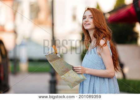 Attractive redhead girl holding a guide map while standing outdoors on a city street