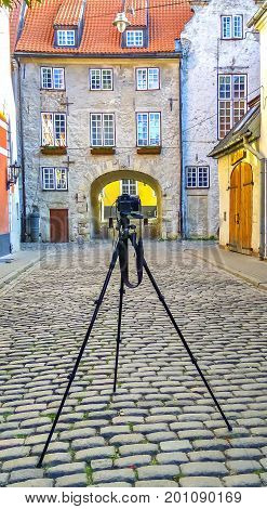 In old Riga city tourists can find a unique atmosphere of Middle Ages and  famous ensembles of Gothic architecture. On foreground is the DSLR camera with tripod