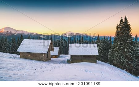 Wooden houses on a snow-capped hill in a carpathian mountain valley. Beautiful winter landscape. Carpathians Ukraine Europe.