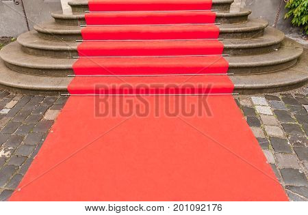 Red carpet prepared for an event outside a building with stairs.