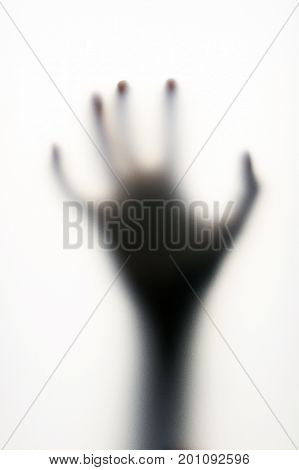 Diffused shadow of hand with thin fingers behind the frosted glass. Fear, phobia, danger or loneliness concept.