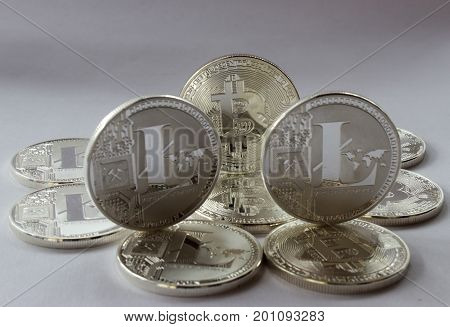 On a white background are silver coins of a digital crypto currencies - Litecoin and Bitcoin. In addition to the lying coin there are one standing bitcoin and two standing litecoins.