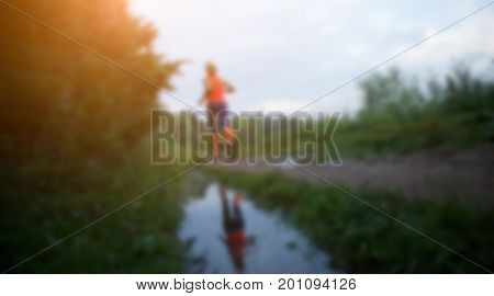 Defocused photo from back of athlete running along path in park