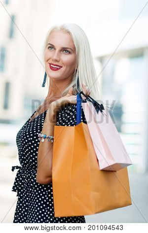 Photo of model on shopping with purchases on street near buildings during day