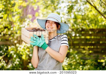 Young brunette agronomist in hat with box of potatoes in summer