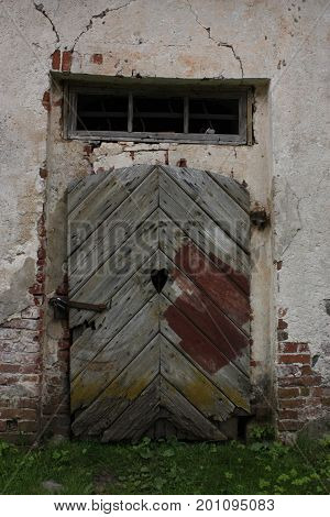 An old country barn door with a window as a heart