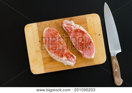 Pork loin on cutting board with spices and knife on dark background. Overhead food shots. Cooking