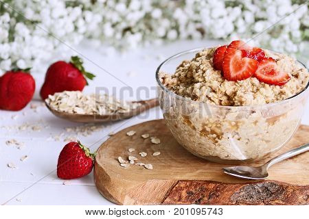 Hot breakfast of healthy oatmeal and heart shaped strawberries. Selective focus with extreme shallow depth of field.