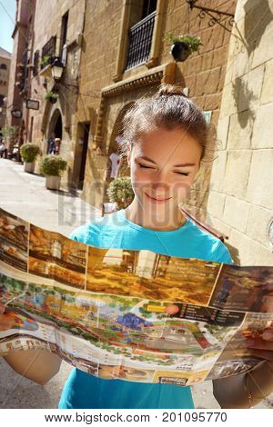 Travel in sunny Spain. Tourist holding travel map. Beautiful smiling girl on holidays in Europe