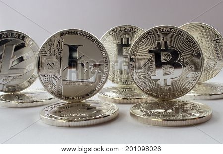 On a white background are silver coins of a digital crypto currencies - Litecoin and Bitcoin. In addition to the lying coins there are standing bitcoin and litecoin.