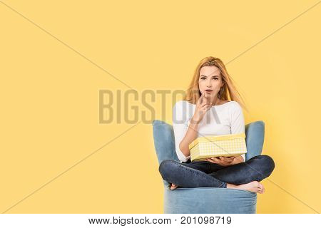 Young woman sits on chair with giftbox in hand and wonder what is inside