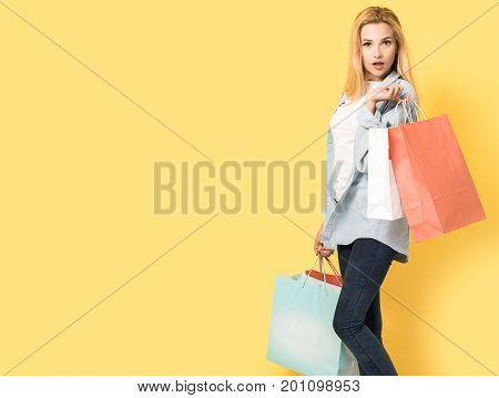 Young woman holding shopping bags on yellow background