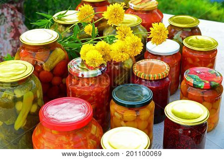 Home-made canned vegetables and jam in glass jars
