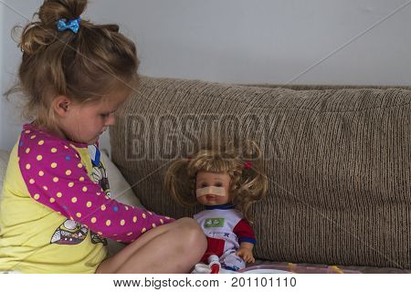 Young caucasian girl playing a doctor with doll