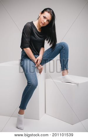 lifestyle, fashion and people concept: beautiful woman wearing casual clothes, posing on white background with big cube