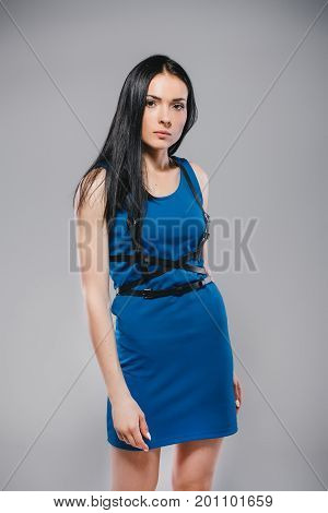 lifestyle, fashion and people concept: attractive woman wearing dark blue dress and swordbelt, posing on white background