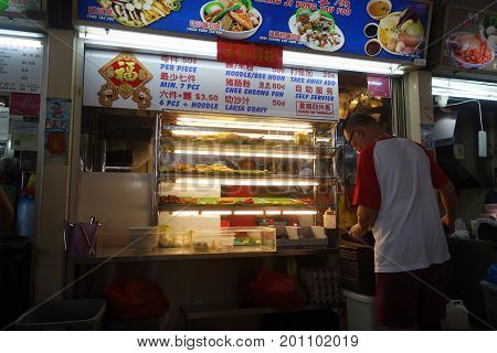 Seller Preparing Food At His Store In Hawker Center In Singapore