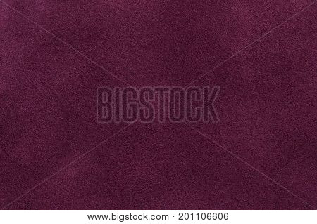 Background of dark purple suede fabric closeup. Velvet matt texture of wine nubuck textile.